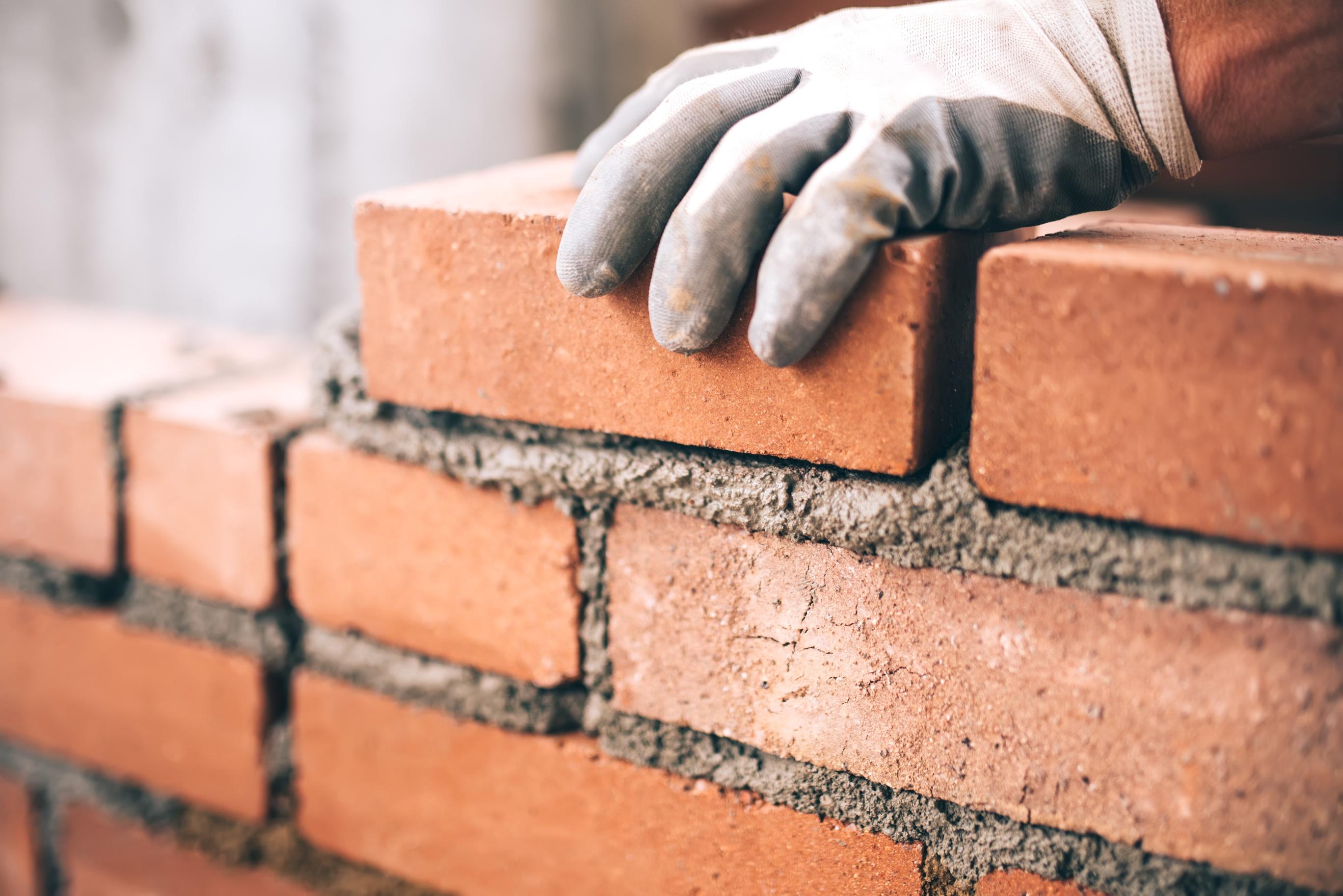 industrial-bricklayer-installing-bricks-on-construction-site-75236615
